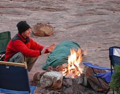 mountain biker warms hands over camp fire