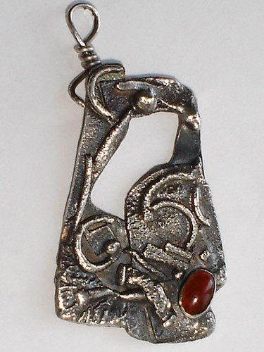 Intricately carved silver earing with red stone in it