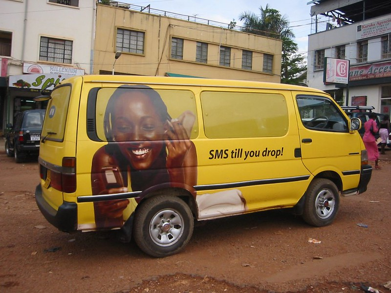 """SMS till you drop"" -- mobile phone ad on van in Kampala, Uganda"