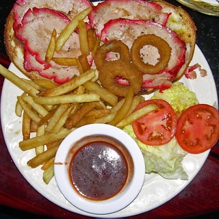 Chinese roast pork on garlic bread with fries, onion rings, tomato, and lettuce