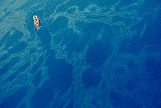 A tanker cuts a path through greasy ocean surface, as oil still pours out from the broken Horizon pipe line below.