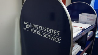 USPS logo on packaging display, APC in background | by Aranami