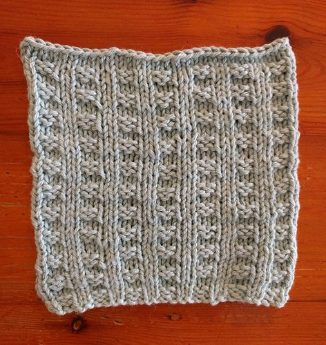 A blue dishcloth in a waffle knitted pattern.
