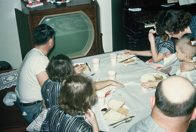 Gathered around the TV set: whole family watching TV and eating dinner, December 1953.