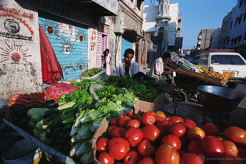 Vendor and his vegetable stand | by World Bank Photo Collection