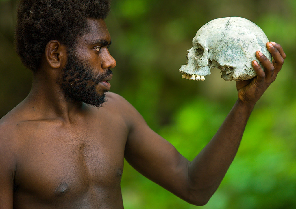 Man holding a human skull in Amelbati cannibal site, Malampa Province, Malekula Island, Vanuatu