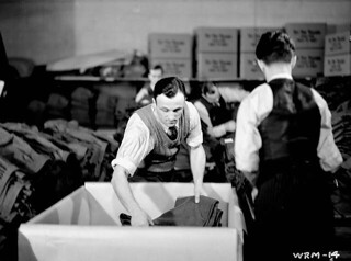 Men sorting and packing new military uniforms to be shipped to the Canadian Army HQ, December 1939 / Hommes qui trient et emballent des uniformes militaires neufs à expédier au QG de l'Armée canadienne, décembre 1939