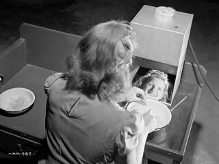 Female worker tests lenses in the Instruments Division of the Canadian Arsenals Ltd. optical plant. / Une ouvrière conduit un essai sur des lentilles dans l'usine de la filiale d'instruments d'optique de la Canadian Arsenals Ltd