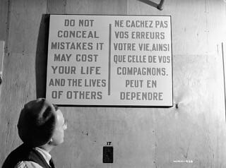A worker reads a caution notice at the Cherrier bomb-making plant, Montreal, Quebec, May 1941 / À l'usine de fabrication de bombes Cherrier, un ouvrièr lit une mise en garde, Montréal, Québec, mai 1941