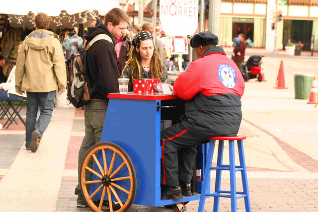 Photo of a man in a red jacket seated on a stool at a cart and conversing with two members of the public outside of a pop-up market.