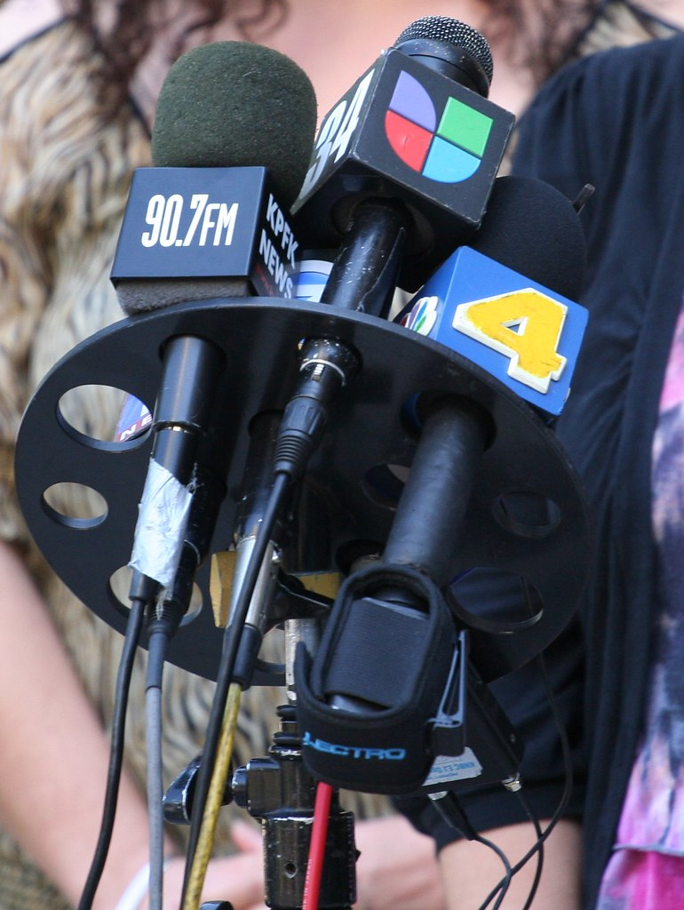 Television news microphone bouquet at press conference in