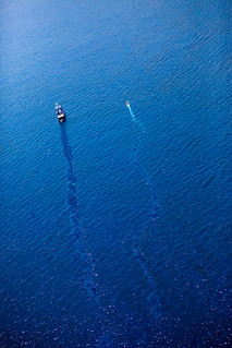 The pathway of the boat stirs up the oily surface | by Kris Krug