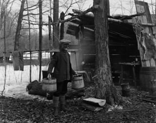 A habitant carrying maple syrup buckets using a yoke standing next to a maple sugar shed / Un habitant, debout à côté d'un abri, porte des seaux remplis de sirop d'érable à l'aide d'une palanche