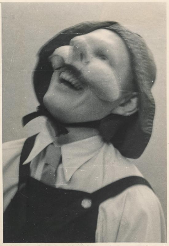 Man laughing while wearing a strange mask