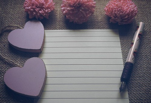 Feminine scene: pink dry flowers, wooden pink hearts, fountain pen, lined paper on sackcloth textured rustic background.