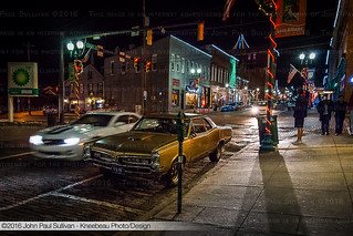 1967 Pontiac GTO parked uptown with Christmas Lights and Camaro going by