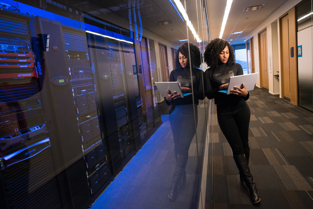 A adult black woman leans against a glass wall of a server room holding an open laptop.