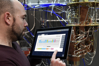 IBM Quantum Computing Research Scientist Antonio Córcoles uses the IBM Quantum Experience on a tablet in the IBM Quantum Lab that shows an open dilution refrigerator (Jon Simon/Feature Photo Service for IBM)