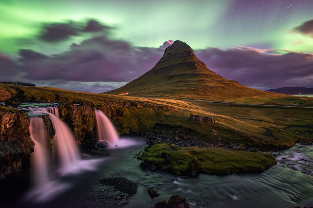 Aurora at Kirkjufell mountain with dramatic clouds.