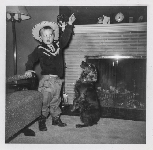 Little boy in a cowboy costume playing with his dog