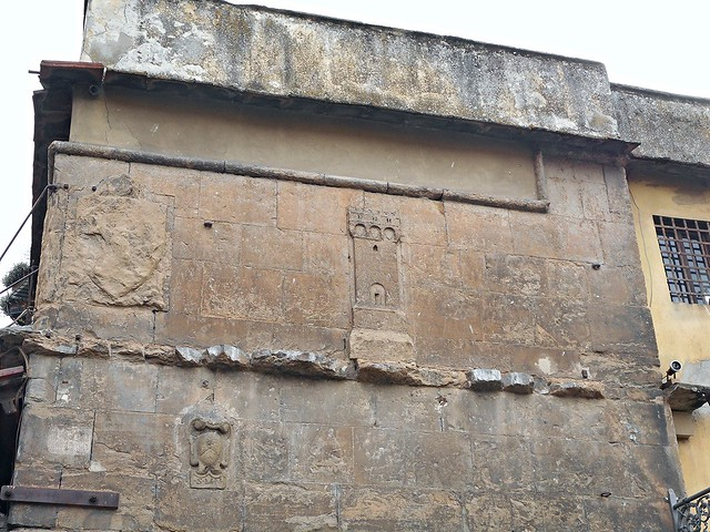Wall with sculpted tower and coat of arms at