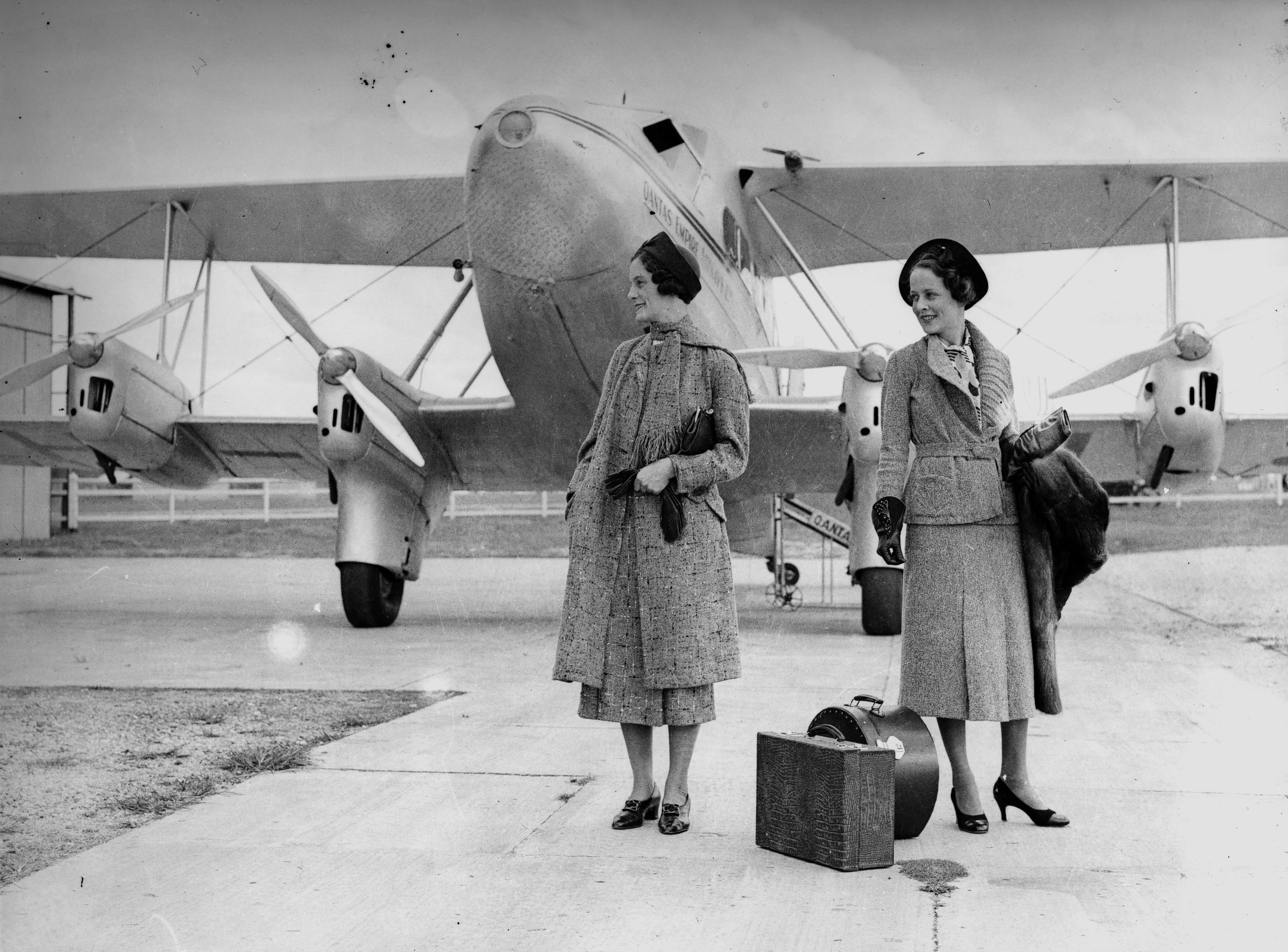 Models posing for a fashion shoot in front of a Qantas biplane 1936