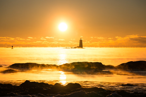 ocean winter light sky lighthouse cold water sunrise maine newengland newhampshire nh coastline atlanticocean seasmoke whalebacklight robertallanclifford robertallancliffordcom