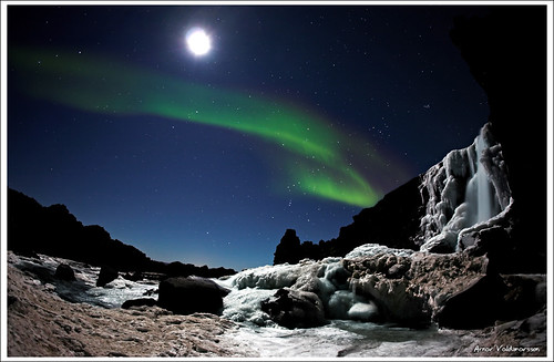 Moonshimmering waterfall and Aurora Borealis | by Arnar Valdimarsson