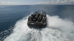 A landing craft air cushion (LCAC) disembarks from the well deck of USS Bonhomme Richard (LHD 6) to return Marines and their equipment ashore at White Beach Naval Facility. (U.S. Navy/MC3 Jeanette Mullinax)