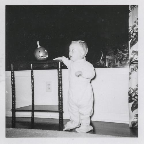 Little boy is startled by a tiny jack-o-lantern