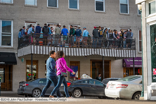 Students party on the balcony above Court Street during a 60º spring day in January