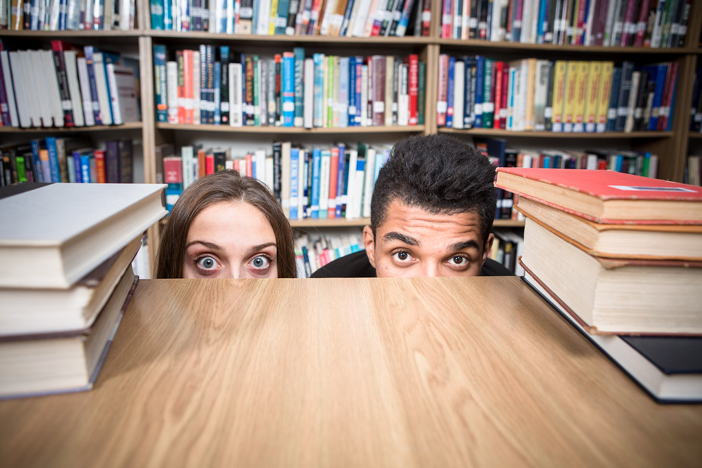 Students hiding behind the table in library
