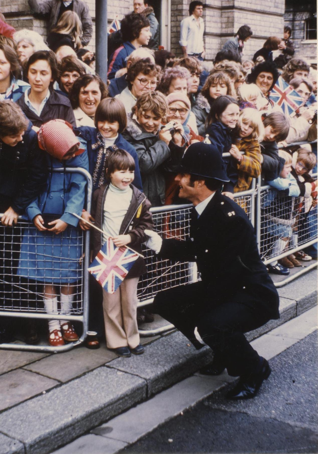 Policeman & child outside Grimsby Town Hall, awaiting arrival of Her Majesty The Queen 1977 (archive ref CCHU-4-1-9-2)