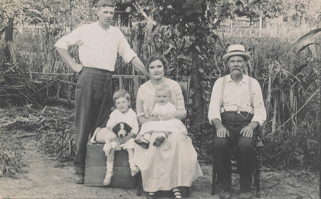 Family posing with a puppy in a garden
