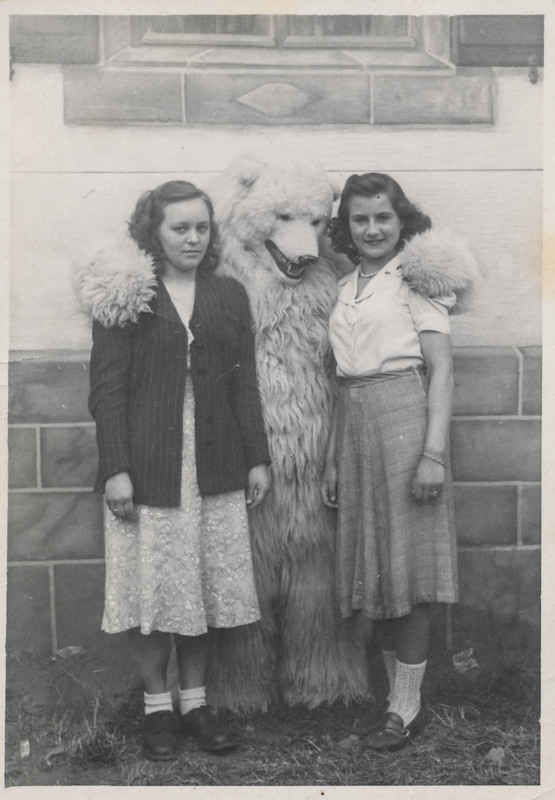 Two women pose with a man in a polar bear costume
