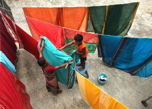 A domestic worker and her son drying clothes on a line | by ILO in Asia and the Pacific