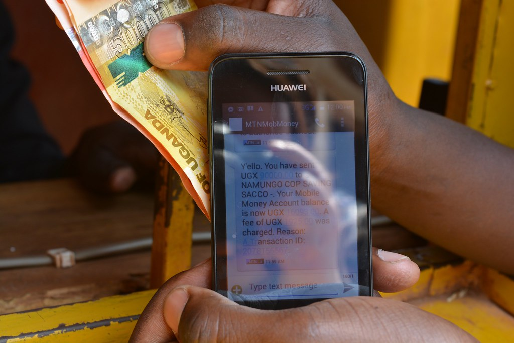 MTN mobile money transaction | Man holds a Huawei smartphone