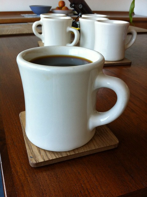 A photo of some classic white American diner mugs with concave sides