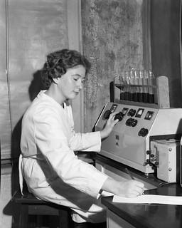 Miss M. Machon operating spectro-photometric measurement machine