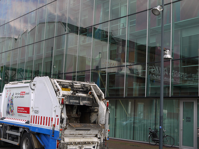 2016.04 - Amsterdam photo of reflections & garbage truck in front of reflecting glass-wall on Oosterburgereiland; geotagged free urban picture, in public domain / Commons; Dutch photography, Fons Heijnsbroek, The Netherlands