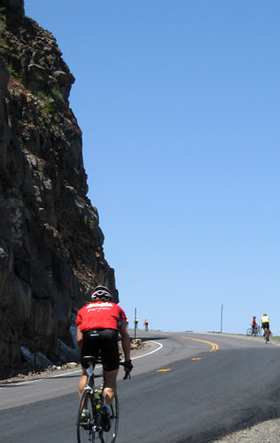 lone biker climbs past cliff