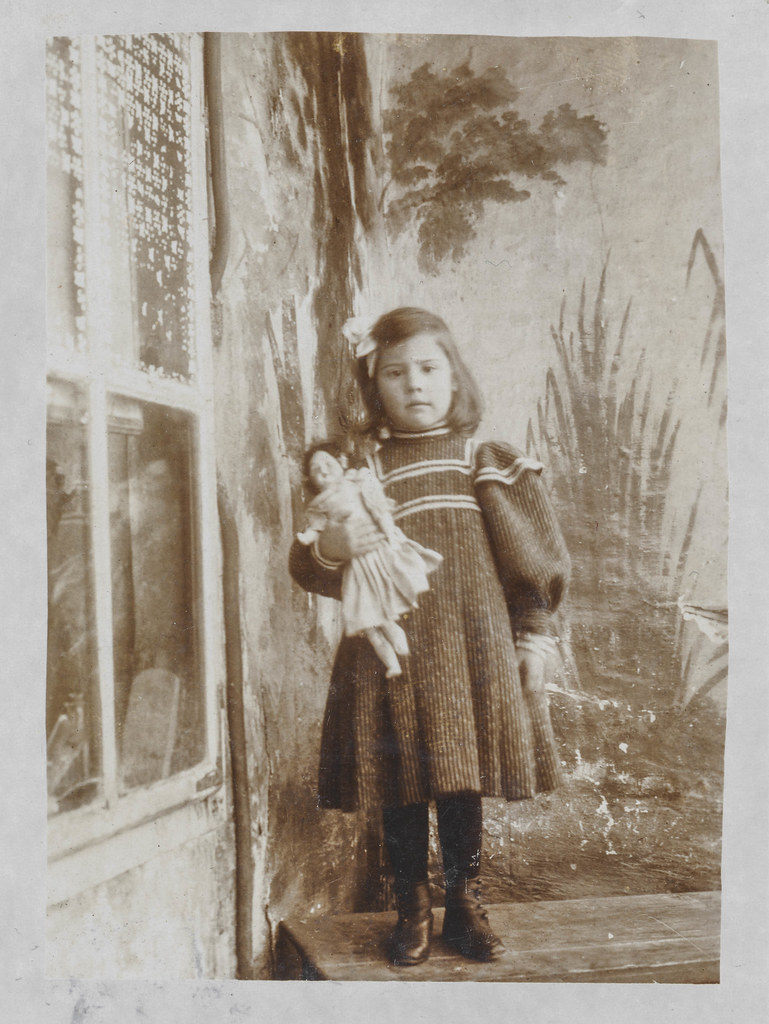 Little girl with a doll stands on a bench
