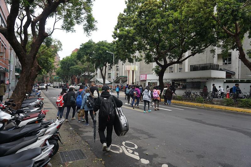 每天中午下課時段,本部學生人潮便湧出近藥局一側門,穿越師大路。圖-漳玨賢攝