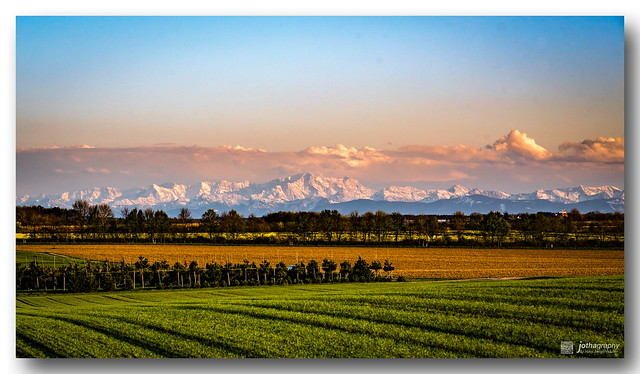 Colorful bands - Snowy alps in spring sunset