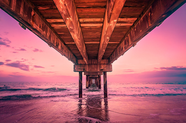 Underneath the St. Johns County Ocean Pier at sunset in St. Augustine Florida
