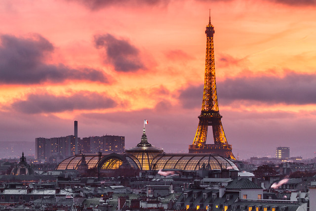 Sunset on Eiffel Tower and Grand Palais glass roof from top of Printemps Department store.