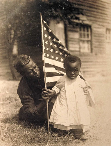 African American mother and child holding an American flag | by oakenroad