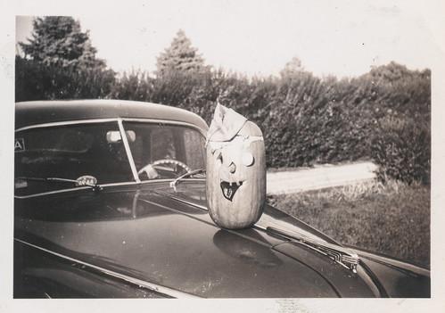 Jack-o-lantern sitting on the hood of a car
