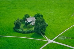 A lonely house in the middle of some grass land seen from Hohensalzburg castle, Salzburg, Austria
