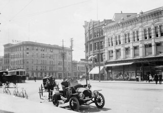 A car, a horse and carriage, and three bicycles parked on a street / Une voiture, un cheval, une charrette et trois bicyclettes stationnés dans la rue